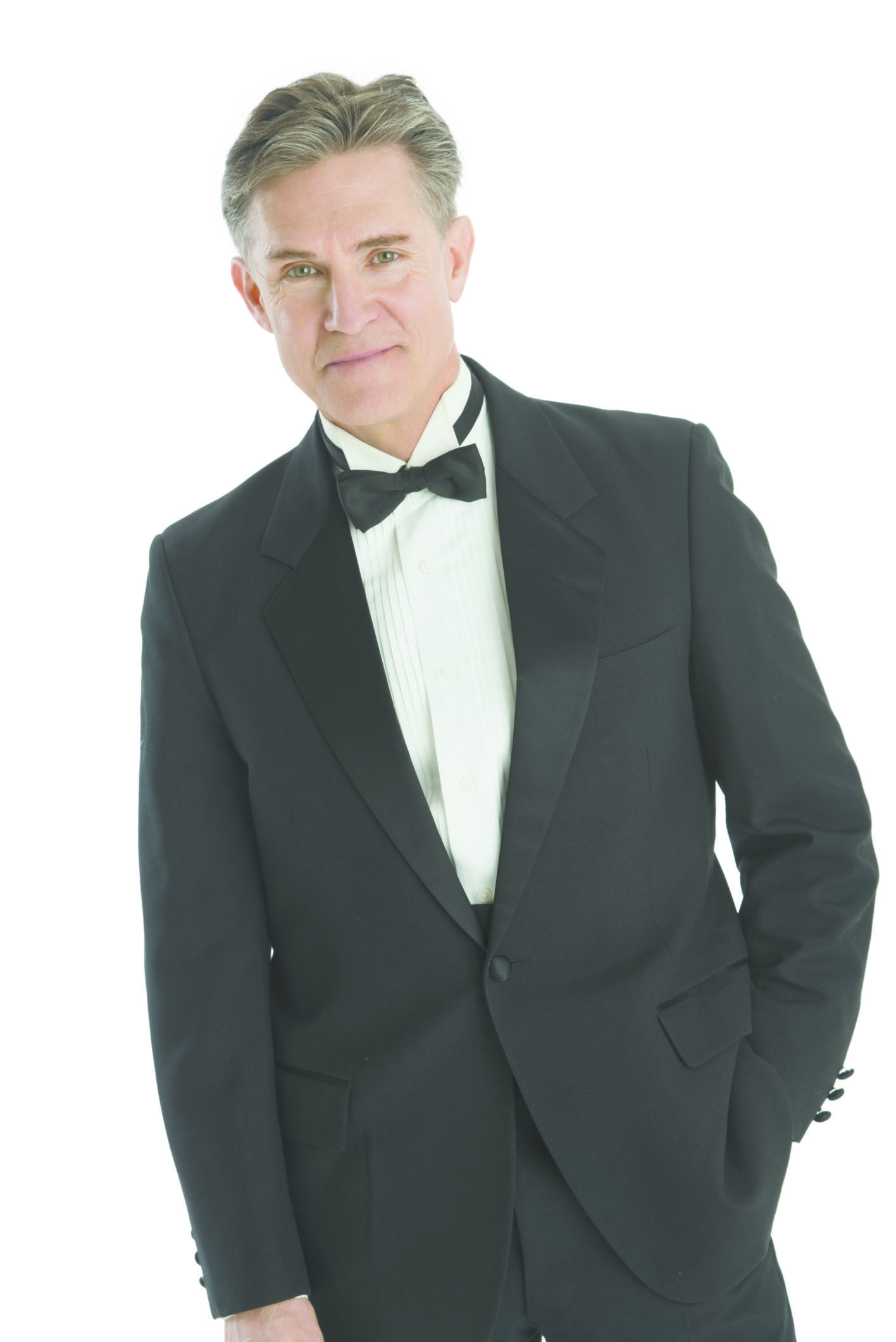 Confident Man In Tuxedo Standing Against White Background