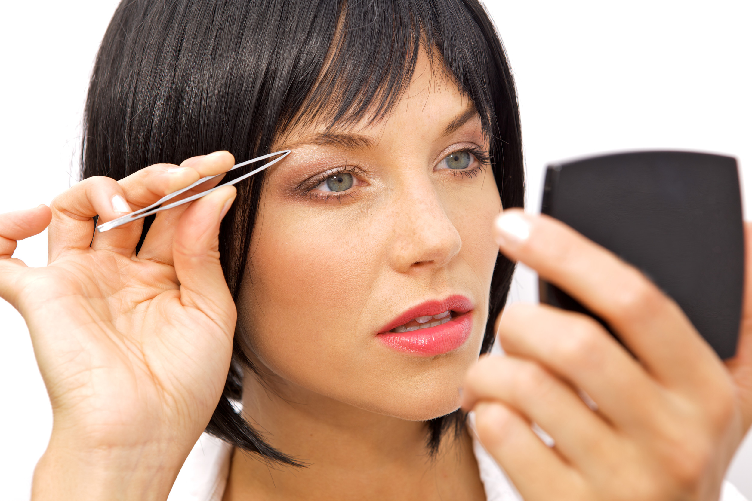 A Beautiful Woman Tweezing her eyebrows with tweezers in her hand