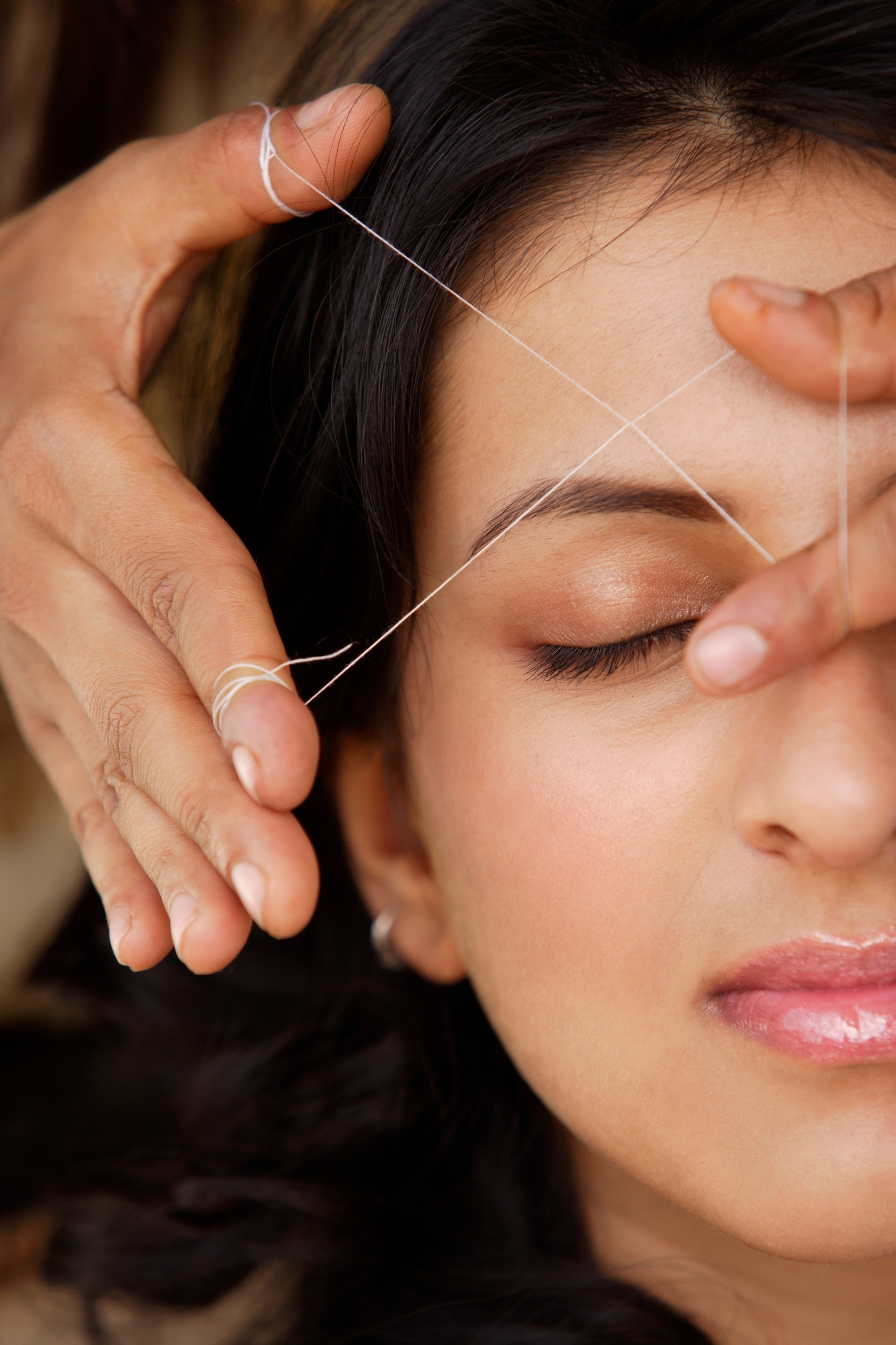 Woman getting eyebrow threading treatment
